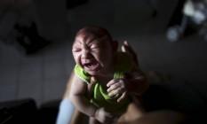 João Pedro, de dois meses, chora no colo da mãe Daniele Santos, em Recife Foto: Nacho Doce / Reuters / 9-2-2016