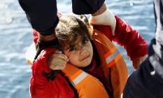 Guarda costeira grega resgata criança e outros imigrantes durante operação de emergência no Mar Egeu Foto: GIORGOS MOUTAFIS / REUTERS