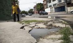 Pedestre caminha por calçada esburacada que acumula poças de esgoto na Estrada do Portela Foto: Hermes de Paula / Agência O Globo