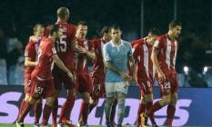 Zagueiro Hugo Mallo, ao centro, do Celta de Vigo, gesticula, enquanto jogadores do Sevilla comemoram o gol de empate Foto: CESAR MANSO / AFP
