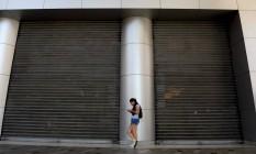 Jovem aguarda do lado de fora de shopping fechado em Caracas Foto: FEDERICO PARRA / AFP