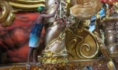 Funcionário da Beija-Flor recupera pintura de adereço da escola: carros costuma ficar danificados após apresentação no Sambódromo Foto: Agência O Globo/Elis Bartonelli