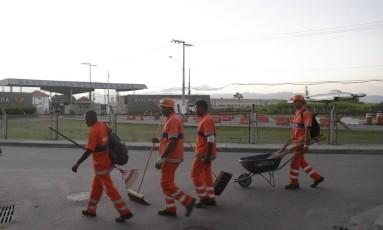 Mutirão. Com a Base Aérea ao fundo, garis saem da localidade Caminho do Zepellin, em Santa Cruz, após realizarem trabalhos de limpeza na região Foto: Marcelo Carnaval
