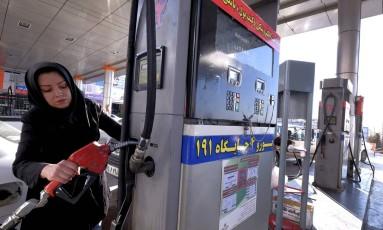 Mulher abastece o carro em posto de gasolina de Teerã. Foto: Raheb Homavandi/Reuters