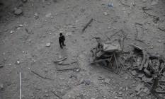 Menino sírio olha destruição deixada por bombardeio sírio ao subúrbio sitiado de Douma, em Damasco Foto: BASSAM KHABIEH / REUTERS
