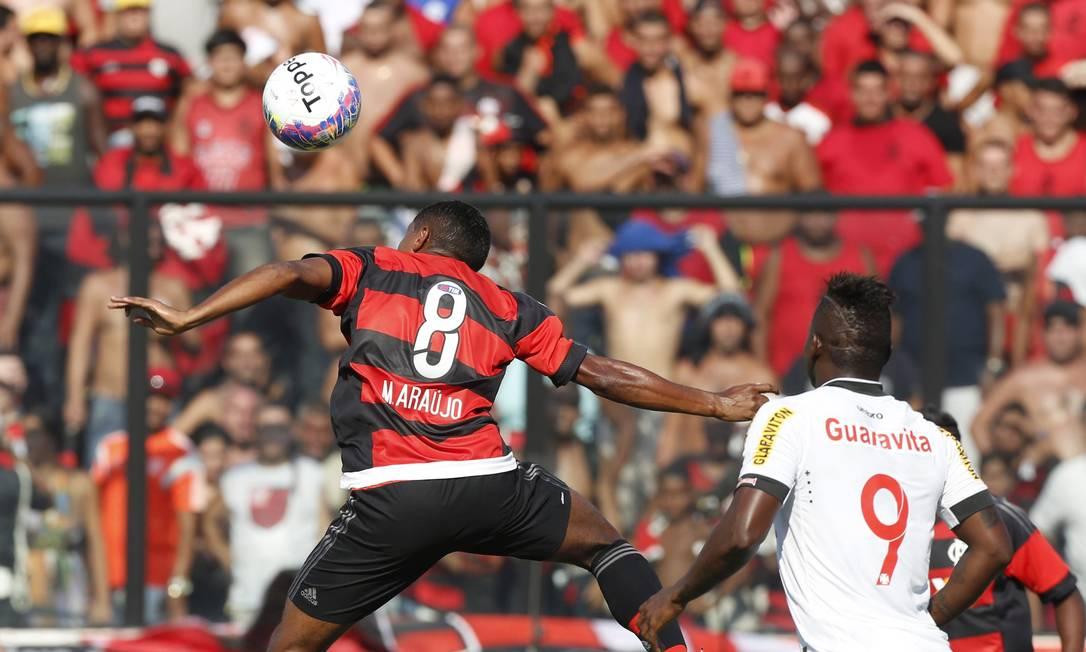 Márcio Araújo tenta a cabeçada enquanto é observado por Riascos Marco Antônio Rezende/ O Globo