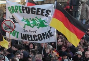 Grupo de extrema-direita segura cartaz que atrela refugiados a estupradores, em marcha de janeiro em Colônia Foto: Juergen Schwarz / AP