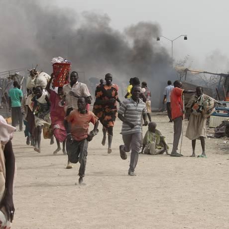 Civis fogem de região atingida por confrontos Foto: JUSTIN LYNCH / AFP