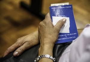 Com a carteira de trabalho nas mãos, mulher aguarda atendimento em agência de emprego em São Paulo Foto: Paulo Fridman / Bloomberg