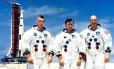 Tripulação da missão Apolo 10 — Eugene Cernan, John Young e Thomas Stafford — fotografada no Centro Espacial Kennedy, tendo ao fundo o foguete posicionado no Launch Pad 39 B