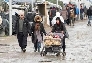 Refugiada leva filhos em carrinho no campo de Calais, no Norte da França Foto: DENIS CHARLET / AFP