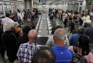 Passageiros aguardam suas malas na esteira de bagagem do Aeroporto Internacional do Galeão Foto: Agência O Globo / Gustavo Miranda/21-11-2013
