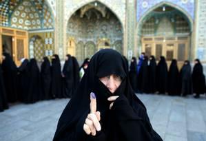 Mulher iraniana mostra a impressão digital pintada — registro de voto nas eleições parlamentares desta sexta-feira, que escolherão os novos membros do Parlamento e da Assembleia de Especialistas de Teerã Foto: Ebrahim Noroozi / AP