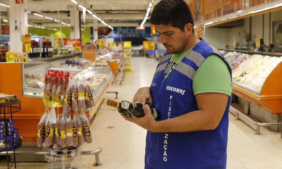 Fiscal do Procon RJ verifica o preço de duas marcas de azeite expostas no supermercado Extra. Uma delas, a da marca Pons, não tinha o preço cadastrado e foi recolhida das prateleiras Foto: Domingos Peixoto / Agência O Globo