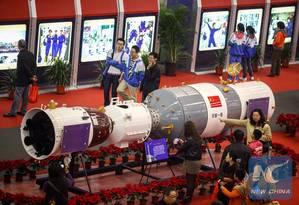 Visitantes observam modelo da nave espacial tripulada Shenzhou-10, acoplada ao módulo espacial Tiangong-1 durante exibição em Tianjin, no norte da China em 9 de novembro de 2013 Foto: Reprodução / Li Xiang / Agência Xinhua [http://goo.gl/4QYdUP]