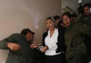 Gabriela Zapata, ao centro, é escoltada ao sair do tribunal no domingo Foto: Juan Karita / AP