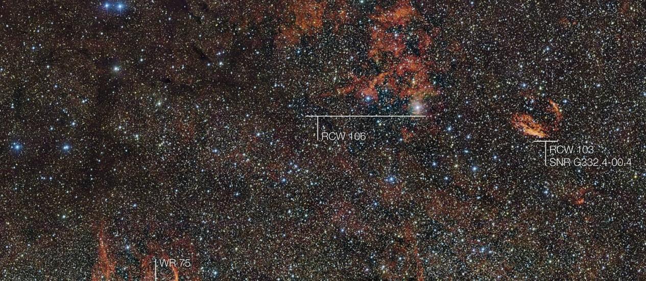 Imagem da região do céu da constelação de Norma mostra a brilhante nuvem de gás e poeira RCW 106, iluminada pela intensa radiação emitida por estrela gigante ainda escondida dentro dela em luz visível, acompanhada de estruturas semelhantes RCW 103 e RCW 104 Foto: ESO