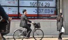 Executivo passa de bicicleta em frente a painel eletrônico com o desempenho da Bolsa de Tóquio Foto: KAZUHIRO NOGI / AFP