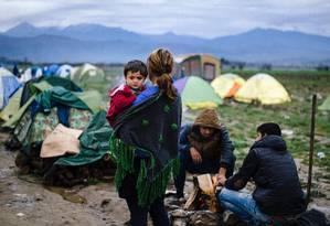 Mulher leva filho em campo de imigrantes na fronteira entre a Grécia e a Macedônia Foto: DIMITAR DILKOFF / AFP