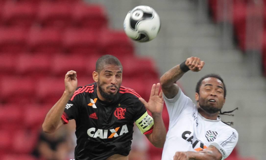 O capitão Wallace, do Flamengo, disputa a bola com o veterano Carlos Alberto, do Figueirense Jorge William / Agência O Globo