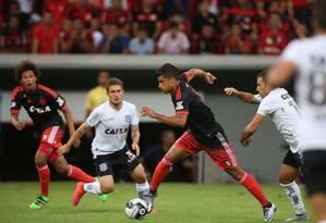Observado por Willian Arão, Ederson parte com a bola dominada no empate entre Flamengo e Figueirense Foto: Michel Filho
