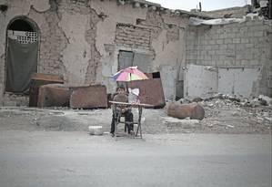 Na zona rural de Damasco, menino deslocado tenta vender alguns bens em frente a prédio danificado, enquanto cerca de 80% da população infantil síria sofre com a guerra Foto: UNICEF