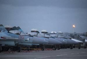 Aviões de combate russos e bombardeiros são vistos na base aérea de Hemeimeem, na Síria Foto: Pavel Golovkin / AP