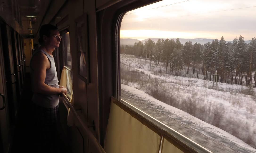 Passageiro observa a paisagem no trem da Transiberiana: viagem é imersão na paisagem e cultura russas Foto: Juarez Becoza / .