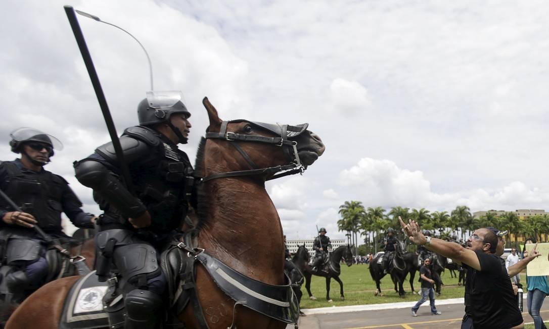 Policiais a cavalo separam manifestantes pró e contra o governo Foto: RICARDO MORAES / REUTERS