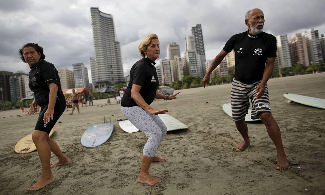 Edmea Pereira, de 69 anos, Elsa Rodrigues, de 61, e Osmidio Conde, de 71, treinando o posicionamento na areia antes de entrar na água. Eles são alunos da escolinha de surfe voltada para a terceira idade em Santos. NACHO DOCE / REUTERS