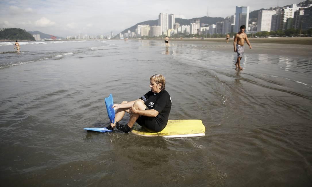 Regina Palomares, de 68 anos, calça os pés-de-pato sentada sobre sua prancha de body board NACHO DOCE / REUTERS