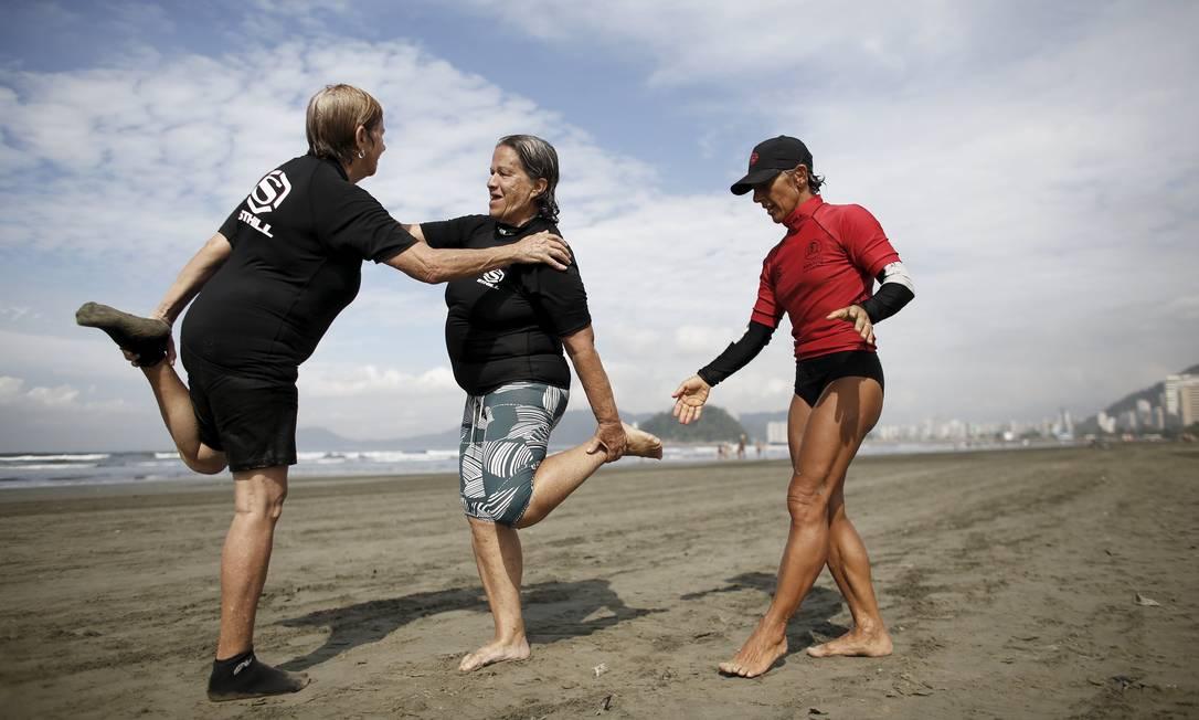A professora Denise (de vermelho) com os alunos Maria Ines, de 69 anos, e Regina Palomares, durante uma sessão de alongamento, parte importante da aula de surfe NACHO DOCE / REUTERS