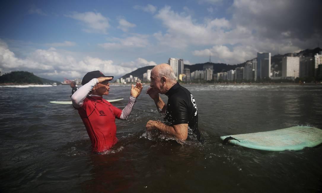 A professora Denise, de 55 anos, orientando a aluna Claudines Garcia, de 64 anos, durante a aula de surfe NACHO DOCE / REUTERS