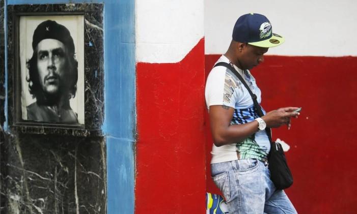 Mudanças. Cubano olha o celular ao lado de imagem de Che Guevara numa área de wi-fi no Centro de Havana: novos hábitos transformam aos poucos o dia a dia na ilha comunista Foto: Daniel Ramalho
