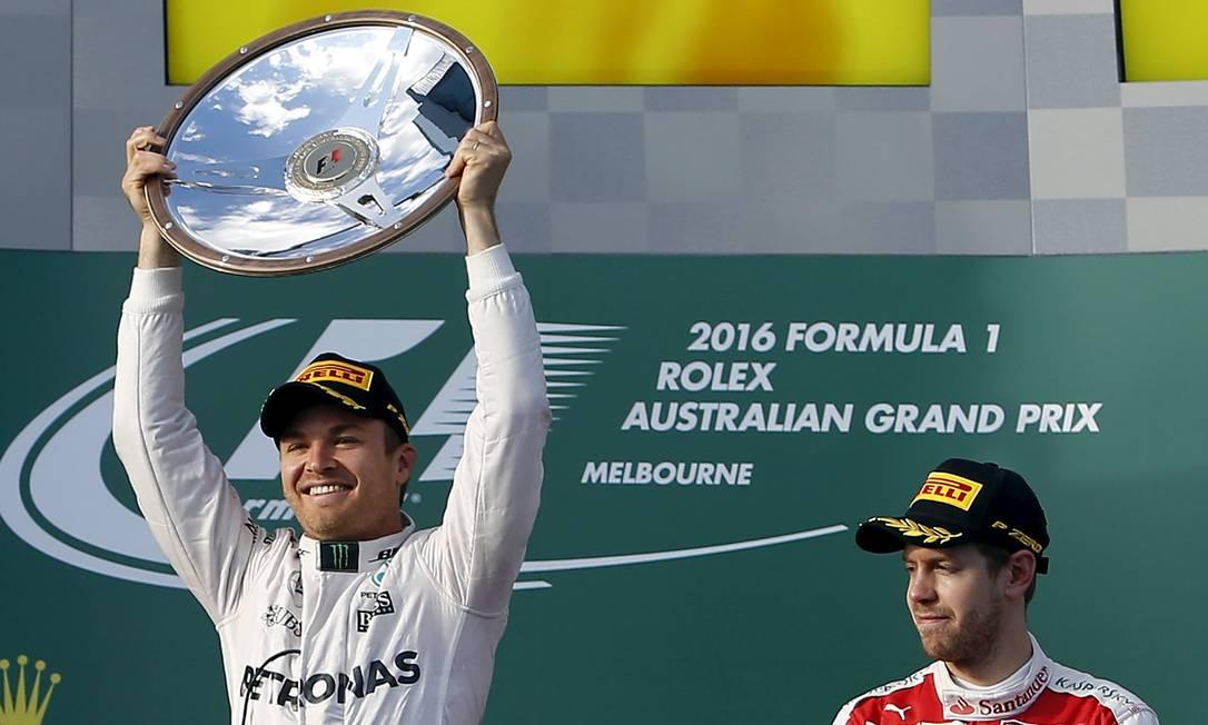 Observado pelo compatriota Sebastian Vettel, da Ferrari, Nico Rosberg, da Mercedes, ergue o troféu de campeão do GP da Austrália JASON REED / REUTERS