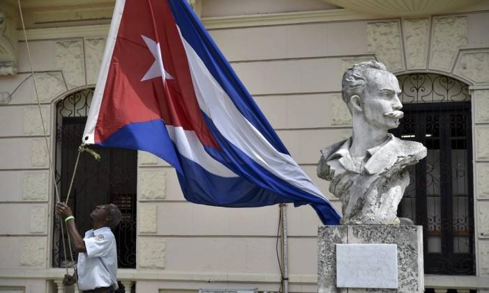 Cubano segura bandeira nacional ao lado do monumento em homenagem a José Martí Foto: YURI CORTEZ / AFP