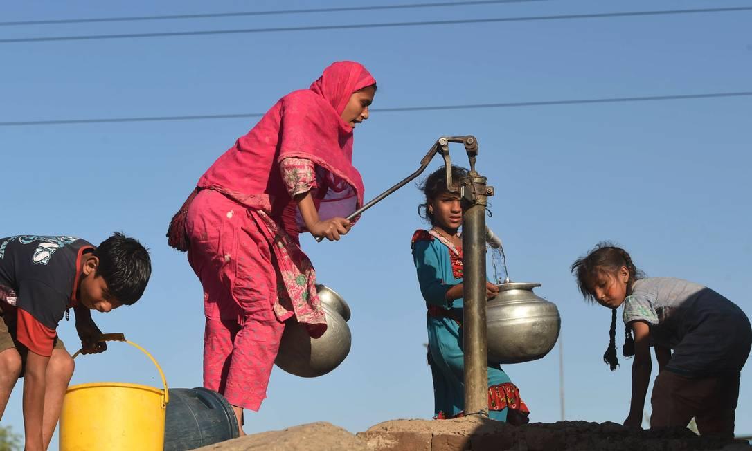 Paquistaneses enchem baldes com uma bomba na mão em uma favela na área de Lahore, no Nordeste do país ARIF ALI / AFP