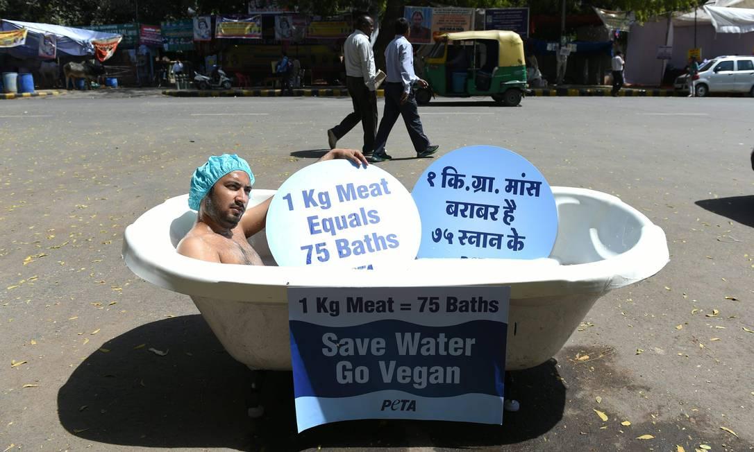 Ativista indiano faz protesto dentro de banheira destacando o gasto de água com pecuária SAJJAD HUSSAIN / AFP
