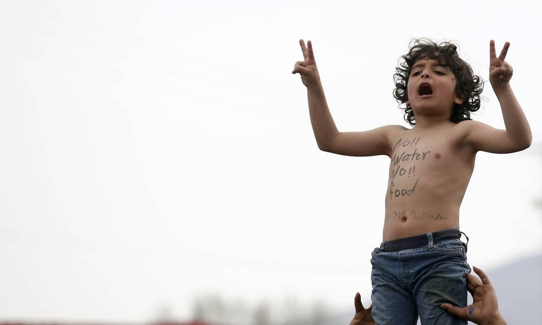 Menino participa de um protesto exigindo a abertura da fronteira entre Grécia e Macedônia. A maioria dos migrantes vem da Síria e denuncia a escassez de água que, assim como a guerra civil, impulsionou a saída da população do país Darko Vojinovic / AP