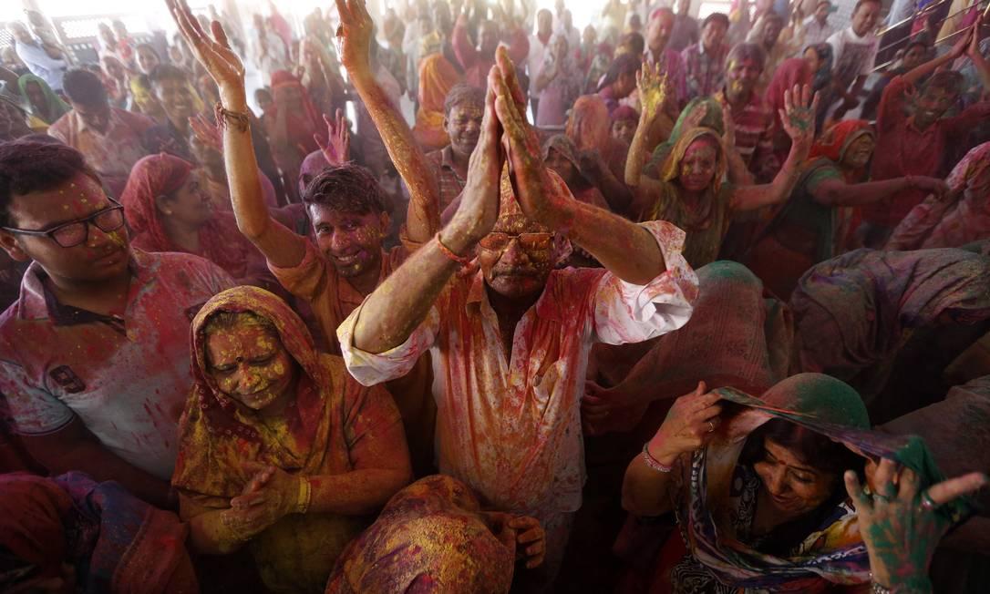 Devotos hindus cobertos de cores cantam músicas religiosas dentro de um templo durante o Holi em Ahmedabad, na Índia AMIT DAVE / REUTERS