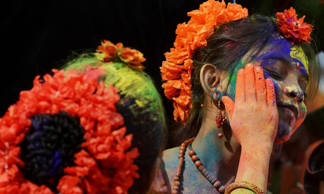 Uma estudante colore o rosto de uma colega durante as festividades do Holi, que comemora a Primavera na Índia DIBYANGSHU SARKAR / AFP