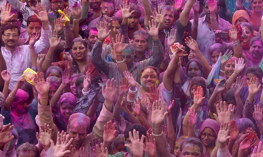 Devotos do hinduísmo cobertos de pó colorido celebram o Holi no Tempo de Durgiayana, em Amritsar NARINDER NANU / AFP
