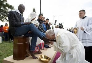 Papa Francisco beija pé de refugiados em cerimônia de lava-pés em um centro perto de Roma Foto: OSSERVATORE ROMANO / REUTERS