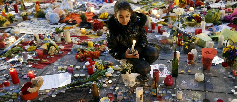 Menina segura uma vela em tributo às vítimas do ataque terrorista em Bruxelas Foto: FRANCOIS LENOIR / REUTERS
