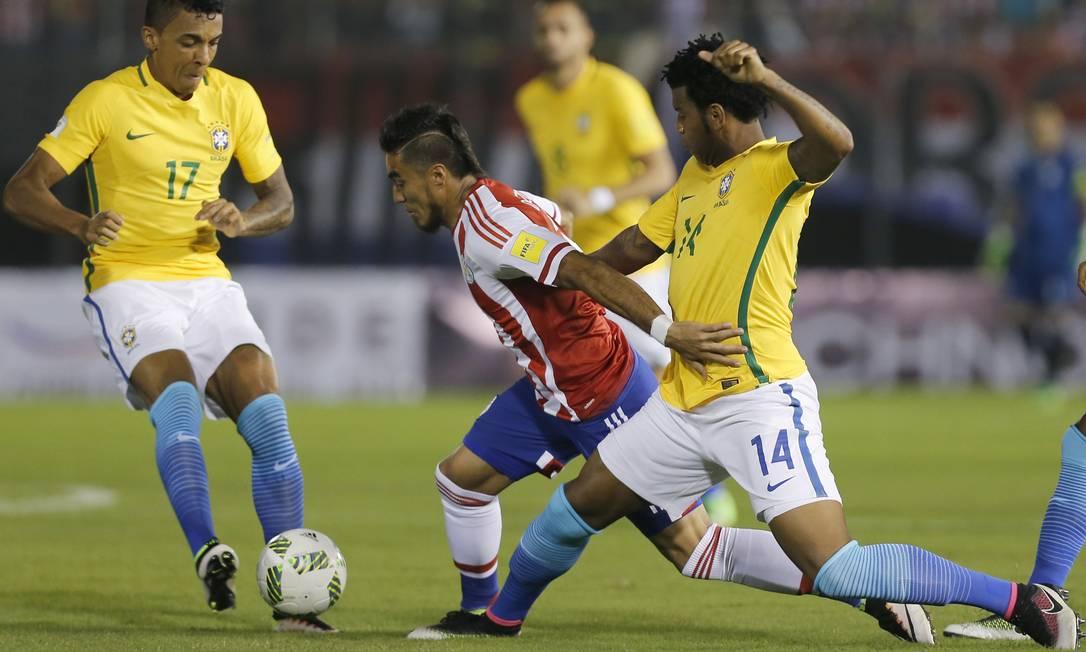 O paraguaio Lezcano é derrubado por Gil, da seleção brasileira, na partida no Defensores Del Chaco, em Assunção Jorge Saenz / AP