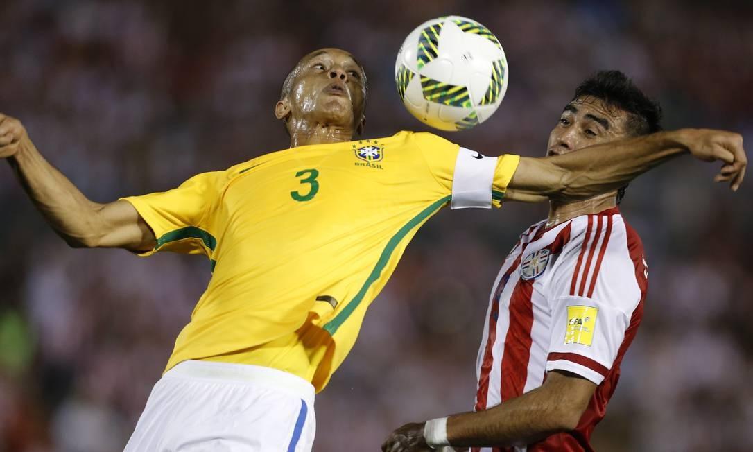 Zagueiro brasileiro Miranda disputa a bola com Dario Lezcano, do Paraguai Foto: Jorge Saenz / AP