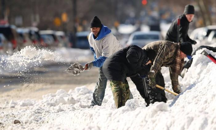 Pessoas tentam abrir espaço em meio a neve Foto: SPENCER PLATT / AFP