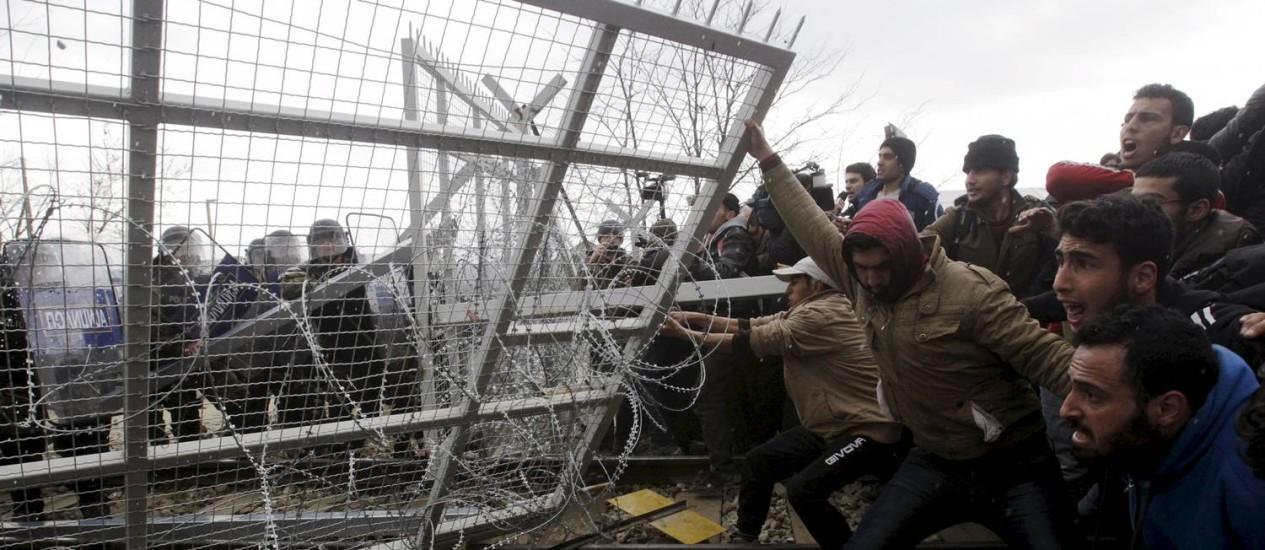 Refugiados destróem cercas em protesto na fronteira entre Grécia e Macedônia, em Idomeni Foto: ALEXANDROS AVRAMIDIS / REUTERS