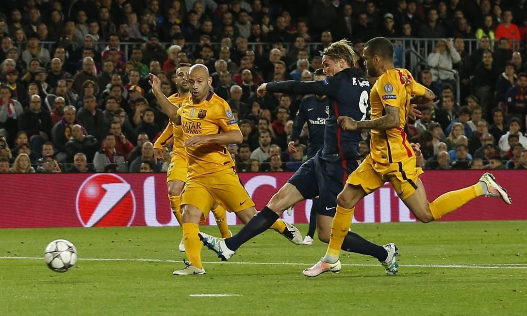 O espanhol Fernando Torres, entre Mascherano e Daniel Alves, chuta para abrir o placar para o Atlético de Madrid contra o Barcelona Albert Gea / REUTERS
