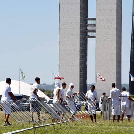 Detentos montam estrutura para separar manifestantes nos dias de votação do impeachment Foto: Evaristo Sá/AFP/10-4-2016